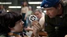 "Zack Mills, left, shows Kyle Chandler a roll of super-8 film in a scene from the movie ""Super 8"". (Francois Duhamel/AP)"