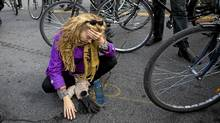 A woman (name withheld) sits on the ground at the end of a memorial ride on Nov. 14, for pregnant cyclist Jenna Morrison, who was recently killed after being struck by a truck at Sterling and Dundas in Toronto. (Michelle Siu for The Globe and Mail/Michelle Siu for The Globe and Mail)