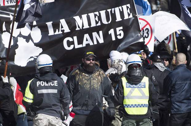 Police hold back far-right protesters during a demonstration in Montreal, Saturday, March 4, 2017.
