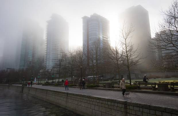 Condo towers are shrouded in dense fog in downtown Vancouver. B.C.'s finances have been supported by skyrocketing real estate prices – and the associated property transfer tax – but there are signs the windfall may not last.