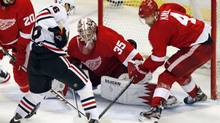 Detroit Red Wings goalie Jimmy Howard (35) and defenceman Jakub Kindl (4) stop Chicago Blackhawks centre Marcus Kruger (16) from scoring in the 3rd period during Game 4 of their NHL Western Conference semifinals playoff game in Detroit, Michigan May 23, 2013. (REBECCA COOK/REUTERS)