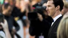 Actor Benedict Cumberbatch, right, poses for photographs on the red carpet at the gala for the new movie The Fifth Estate during the 2013 Toronto International Film Festival in Toronto on Thursday, Sept. 5, 2013. (Nathan Denette/THE CANADIAN PRESS)