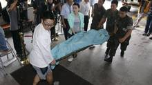 A man is carried to a hospital in Gangneung, South Korea, on June 23, 2014. A South Korean Defence Ministry official says two ambulances were used to bring a fugitive soldier who killed three of his comrades to hospital: one carrying the injured fugitive and the other with another soldier whose body and face were covered by a blanket. The decoy was carried into the hospital as photographers snapped pictures. (LEE SANG-HACK/ASSOCIATED PRESS)