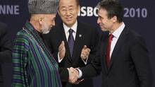 Afghanistan's President Hamid Karzai (L) and NATO Secretary General Anders Fogh Rasmussen (R) shake hands in front of U.N. Secretary General Ban Ki-moon after signing accords during the NATO Summit in Lisbon November 20, 2010. (Yves Herman/Reuters/Yves Herman/Reuters)