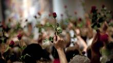 People hold up red roses during a memorial service for the victims of the bomb and shooting massacre, organized by the Norwegian Labour party and its youth organization, AUF, in Oslo, Friday July 29, 2011. (Emilio Morenatti/Emilio Morenatti)