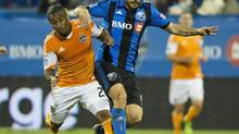 Montreal Impact's Marco Di Vaio, right, and Houston Dynamo's Corey Ashe battle for the ball during second half MLS soccer action in Montreal, Saturday, August 24, 2013. (Graham Hughes/THE CANADIAN PRESS)