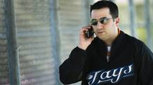 Toronto Blue Jays general manager Alex Anthopoulos talks on his cell phone during baseball spring training in Dunedin, FL, on Wednesday, Feb. 16, 2011. (Nathan Denette/THE CANADIAN PRESS/Nathan Denette)