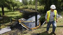 In this July 29, 2012 file photo, a worker monitors the water in Talmadge Creek in Marshall Township, Mich., near the Kalamazoo River as oil from a ruptured pipeline, owned by Enbridge Inc, is vacuumed out the water. (Paul Sancya/AP)