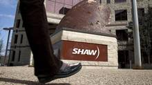 People walk past the headquarters of Shaw Communications in Calgary, Alta., in this file photo. (Jeff McIntosh/THE CANADIAN PRESS)