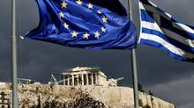 The European Union and Greek flags fly near the Parthenon in Athens on Oct. 31, 2011. (Angelos Tzortzinis/Bloomberg)