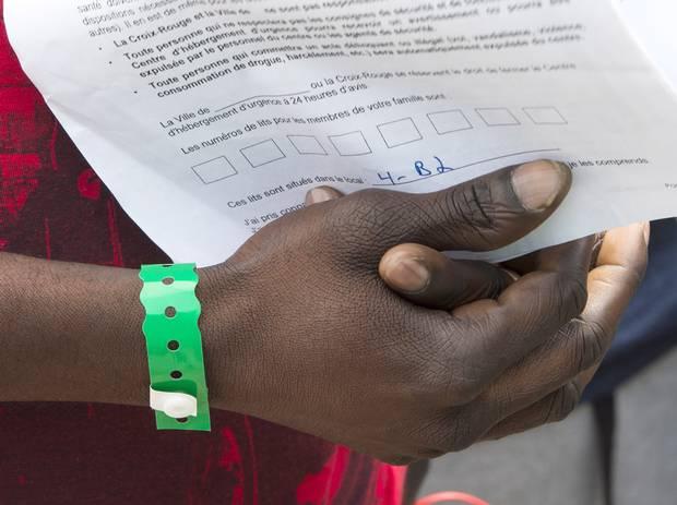 Aa asylum seeker holds on to his paperwork as he leaves Olympic Stadium.