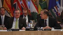 Finance Minister Jim Flaherty, left, and Bank of Canada Governor Mark Carney wait for the start of a meeting with provincial and territorial finance ministers at Meech Lake in Quebec on Dec. 17, 2012. (CHRIS WATTIE/REUTERS)