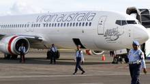 Indonesian Air Force personnel stand guard near a Virgin Australia airplane in Bali, Indonesia, Friday, April 25. (Firdia Lisnawati/THE ASSOCIATED PRESS)