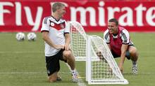 German national soccer players, Lukas Podolski, right, and Bastian Schweinsteiger joke during a training session in Santo Andre near Porto Seguro, Brazil, Monday, June 23, 2014. Germany play in group G of the 2014 soccer World Cup. (Matthias Schrader/AP)