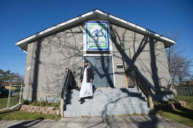 Imam Shazim Khan walks down the stairs at his mosque Masjid Al-Salaam in Peterborough, Ont
