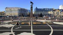 People walk over tarmac with the APEC logo printed on it, in a central square of Vladivostok. (SERGEI KARPUKHIN/REUTERS)