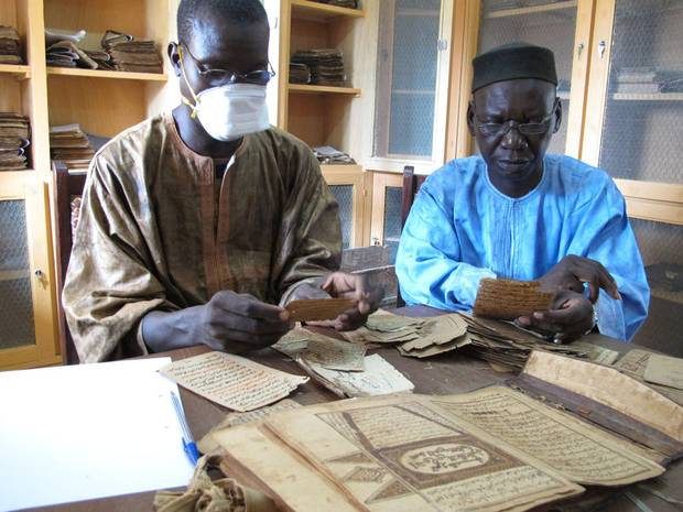 Archivists Aboubakar Yaro and Alphamoye Djeite study ancient manuscripts in a library in the Malian town of Djenne. (Yaro is wearing a mask to protect him from dust.) They are cataloguing the manuscripts as part of a British Library project to digitize copies of 200,000 manuscript pages in Djenne.