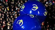 People play with balls bearing the euro symbol at Madrid's Puerta del Sol, shortly before the introduction of euro notes and coins. (ANDREA COMAS/REUTERS)