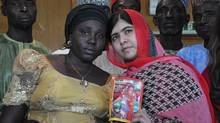 Pakistani activist Malala Yousafzai who survived being shot by the Taliban because she advocated education for girls, holds a picture of kidnapped schoolgirl Sarah Samuel with her mother Rebecca Samuel, during a visit to Abuja, Nigeria, Sunday July 13, 2014. Malala Yousafzai traveled to Abuja in Nigeria to meet the relatives of schoolgirls who were kidnapped by Boko Haram three months ago. (Olamikan Gbemikan/AP)