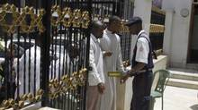Muslim men are searched by security guards, on entering a mosque, in Nairobi, Kenya, Friday. (Khalil Senosi/AP)