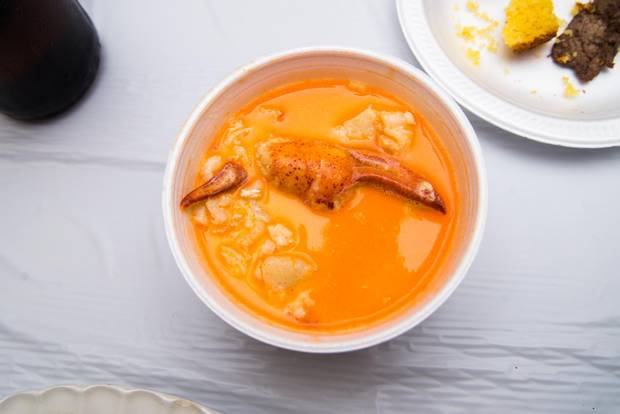 A plump lobster claw peeks out from a bowl of seafood chowder.