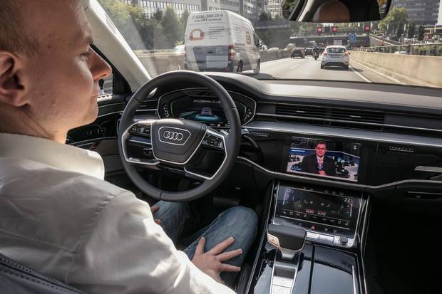 Watching the news while the Audi A8 pilots itself in traffic.