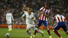 Real's Luka Modric from Croatia, centre left, in action with Atletico's Mario Suarez, centre right, during a Spanish Supercup first leg soccer match between Real Madrid and Atletico Madrid at the Santiago Bernabeu stadium in Madrid, Spain, Tuesday, Aug. 19, 2014. (Andres Kudacki/AP)