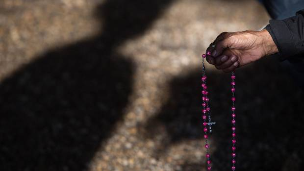 A woman holds a rosary during Mass at Lac Ste. Anne, Alberta on Wednesday, July 22, 2015. Mass is performed in many languages, including Dene and Cree, and incorporate many cultural traditions.