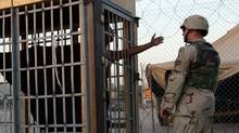 A detainee in an outdoor solitary confinement cell talks with a military policeman at the Abu Ghraib prison on the outskirts of Baghdad, June 22, 2004. (John Moore/AP)