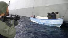 A Greek Navy commando aims his rifle at a suspected pirates detained off the Somali coast in April, 2009 (Ho)