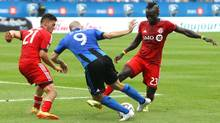 Toronto FC midfielder Alvaro Rey (23) and midfielder Jonathan Osorio (21) and Montreal Impact forward Marco Di Vaio (9) battle for the ball during the second half at the Stade Saputo. (Jean-Yves Ahern/USA Today Sports)