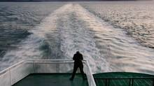 A passenger stands on the back deck of the BC Ferries' Queen of Coquitlam during a crossing from Vancouver Island to the mainland at sunset in June 2004. (Andy Clark/Reuters)