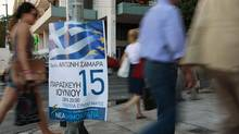 Pedestrians walk past pre-election posters in Athens June 13, 2012. Greece holds general parliamentary elections on June 17. (PASCAL ROSSIGNOL/REUTERS)
