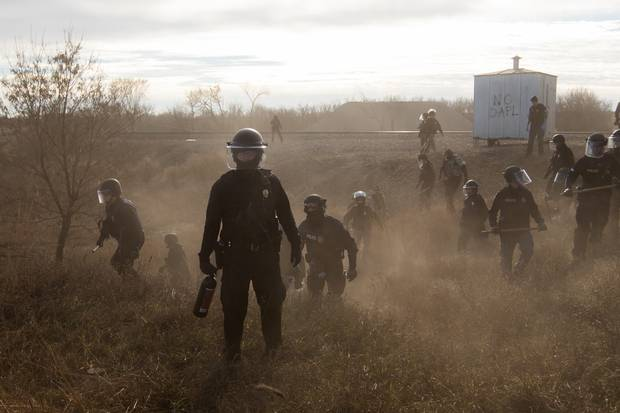 Riot police outside a Dakota Access Pipeline worker camp in Mandan, N.D. confront protesters who were drawing attention to disproportionate sexual violence against indigenous women. The violence is exacerbated by the presence of heavily male work crews that form temporary housing communities around industrial sites.