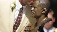 Warren Moon, kissing his bronze bust during his enshrinement into the Pro Football Hall of Fame in 2006 in Canton, Ohio, expects to be at the 100th Grey Cup in Toronto this weekend. (MARK DUNCAN/The Associated Press)
