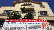 "A ""bank foreclosure sale"" sign is posted in front of townhomes in Los Angeles, Calif. U.S. banks repossessed homes at a near-record pace to drive up July foreclosures. (Kevork Djansezian/Getty Images)"