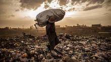 A man from the neighboring slum of Korogocho , Kenya hefts his last bag of trash for the day in Dandora city dump in hopes of selling the mostly rubber scraps for 50 cents. (Micah Albert/Pulitzer Center/Micah Albert/Pulitzer Center)