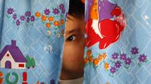 An autistic child peers from between curtains at the Consulting Centre for Autism in Amman, March 30, 2010. (ALI JAREKJI/REUTERS/Ali Jarekji)