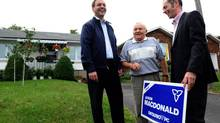 Tim Hudak, left, places a sign on the lawn of Heinz Osuch's, middle, house along with PC candidate Jason MacDonald on September 8, 2011. MacDonald is believed to be a contender for PMO top spokesman. (Sean Kilpatrick/THE CANADIAN PRESS)