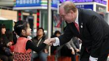 Manulife CEO Don Guloien, shakes hand with He Xing Chen, 5, at the Shanghai Expo (Kevin Lee/Kevin Lee for The Globe and Mail)