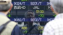 A man is reflected on an electronic stock quotation board outside a brokerage in Tokyo May 16, 2014. Japanese shares stumbled on Friday as the combination of a stronger yen and a second day of declines on Wall Street depressed sentiment, leaving the market poised for the third-week of losses in the past month. (YUYA SHINO/REUTERS)