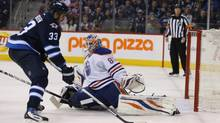 Winnipeg Jets defenseman Dustin Byfuglien controls the puck against Edmonton Oilers goalie Ilya Bryzgalov during the second period at MTS Centre in Winnipeg on Jan. 18. (Bruce Fedyck/USA Today Sports)