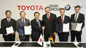 In this photo released by Toyota Motor Corp., Toyota President Akio Toyoda, third left, shakes hands with BMW AG chief executive Norbert Reithofer, third right, as their executives show signed documents during a signing ceremony to jointly develop next-generation batteries for green vehicles in Nagoya, central Japan, Thursday, Jan. 24, 2013.