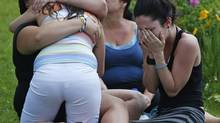 People cry and hug each other while they sit on the grass at the Polyvalente Montignac, the school sheltering the people who were forced to leave their houses after the explosion, in Lac Megantic, July 7, 2013. (MATHIEU BELANGER/REUTERS)