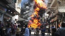 Residents run from a fire at a gasoline and oil shop in Aleppo's Bustan Al-Qasr neighbourhood October 20, 2013. Witnesses said the fire was caused by a bullet fired by a sniper loyal to Syrian President Bashar al-Assad at the Karaj al-Hajez crossing, a passageway separating Aleppo's Bustan al-Qasr, which is under the rebels' control and Al-Masharqa neighborhood, an area controlled by the regime. (Haleem Al-Halabi/REUTERS)