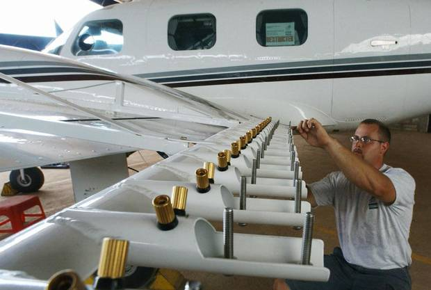 Aircraft technician Steve Bauer of Weather Modification Inc., inspects wing mounted burn-in silver iodide flare racks on a Piper Cheyenne II aircraft before the beginning of cloud-seeding operations at Jakkur Airfield, Bangalore, 17 August 2003. Karnataka's government has contracted the US based company to perform cloud-seeding, which involves the aircraft being piloted into clouds and releasing silver iodide in order to attempt to bring rain to the severe drought hit regions of Karnataka state.