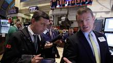 Specialist Michael O'Mara, right, works on the floor of the New York Stock Exchange, Feb. 8, 2012. (Richard Drew/Richard Drew/AP)