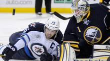 Buffalo Sabres goalie Jhonas Enroth (1) keeps an eye on the puck with Winnipeg Jets left wing Andrew Ladd (L) during the first period of their NHL hockey game in Buffalo, New York January 7, 2012. REUTERS/Doug Benz (Doug Benz/Reuters)