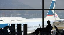 A traveller works on a computer as a Cathay Pacific Airways Ltd. jet, left, and a China Eastern Airlines Corp. Ltd. jet taxi at the gate at Hong Kong International Airport in Hong Kong, China, on Saturday, Dec. 1, 2007. Cathay Pacific Airways Ltd., Hong Kong's largest carrier, and its Flight Attendants Union reached an agreement on a new medical plan, averting a strike or any other form of industrial action. Photographer: Nelson Ching/Bloomberg News