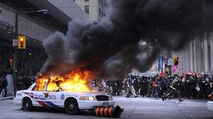 A police car burns in the financial district of Toronto, set ablaze by G20 protestors.